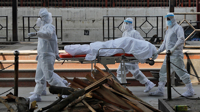 Health workers in protective suits push a stretcher with the body of Virendra Gupta, who died due to the coronavirus disease (COVID-19), for his cremation at the Nigambodh Ghat crematorium in New Delhi, India, June 1, 2020