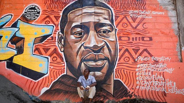 A man sits under a graffiti depicting African-American man George Floyd, who died in Minneapolis police custody, at the Kibera slum of Nairobi, Kenya, June 4,2020.REUTERS/Baz Ratner