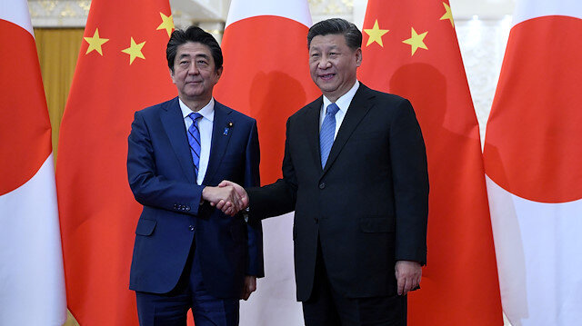 File photo: Japan's Prime Minister Shinzo Abe shakes hands with China's President Xi Jinping