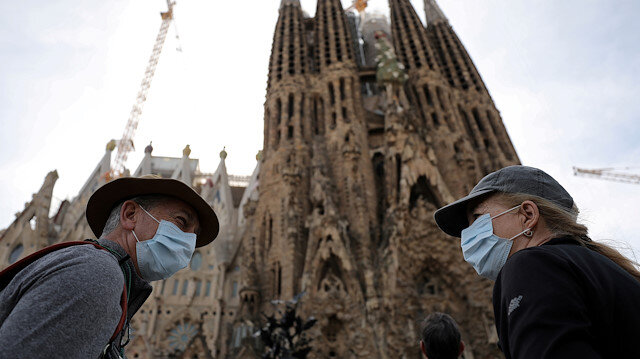 Tourists wear protective face masks as they talk in front of landmark Sagrada Familia basilica, which will stop receiving visitors and suspend its construction work starting from Friday as a precautionary measure due to the coronavirus outbreak in Barcelona