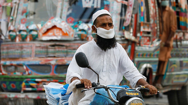 File photo: A man wearing a protective face mask rides a motorbike, as the outbreak of the coronavirus disease (COVID-19) continues, in Karachi, Pakistan June 11, 2020