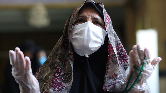 An Iranian worshipper wearing a protective face mask and gloves prays in Qarchak Jamee