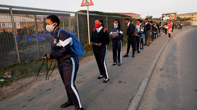 FILE PHOTO: Learners queue before being screened as schools begin to reopen after the coronavirus disease (COVID-19) lockdown in Langa township in Cape Town, South Africa June 8, 2020.