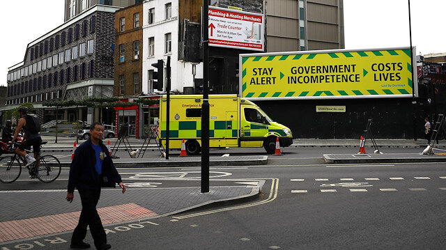 An anti-government poster is seen in London as an ambulance passes