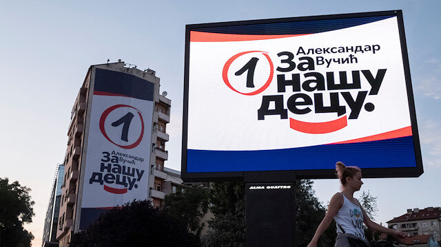 woman walks past election campaign posters of ruling Serbian Progressive Party