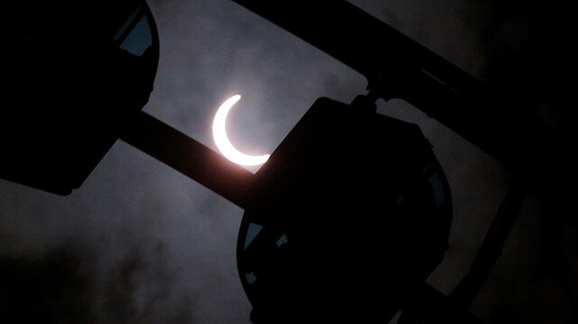 A partial solar eclipse is seen over a ferris wheel, in Hong Kong, China June 21, 2020.