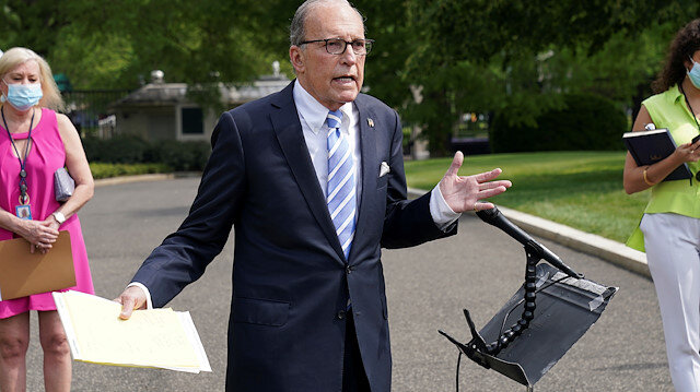 FILE PHOTO: Aides wearing masks stand behind White House economic adviser Larry Kudlow as he speaks to reporters about the economic impact of the coronavirus disease (COVID-19) at the White House in Washington, U.S., May 15, 2020. REUTERS/Kevin Lamarque/File Photo