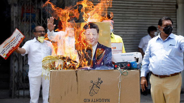 Demonstrators burn products made in China and a defaced poster of Chinese President Xi Jinping