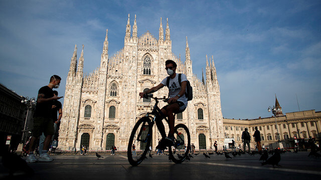 FILE PHOTO: A man wearing a protective face mask rides a bicycle at Piazza Duomo, as Italy eases some of the lockdown measures put in place during the coronavirus disease (COVID-19) outbreak, in Milan, Italy May 18, 2020.