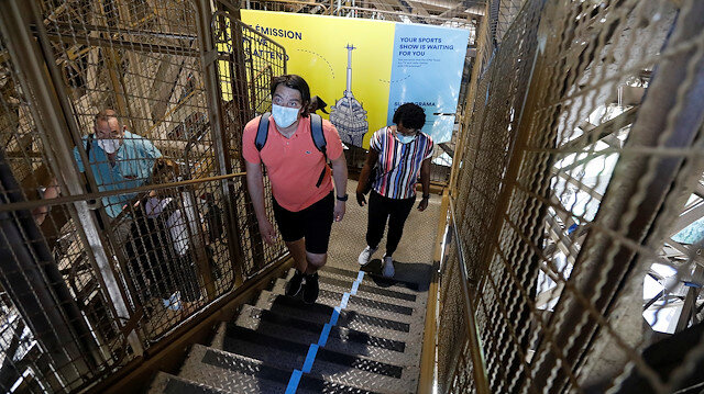 People wearing protective face masks climb the stairs as they visit the Eiffel Tower in Paris on its reopening day to the public following the coronavirus disease (COVID-19) outbreak in France, June 25, 2020