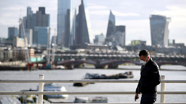 FILE PHOTO: A man wearing a protective mask walks across Waterloo Bridge in front of the City of London financial district during rush hour, as the number of Coronavirus cases grow around the world, in London, Britain, March 17, 2020.