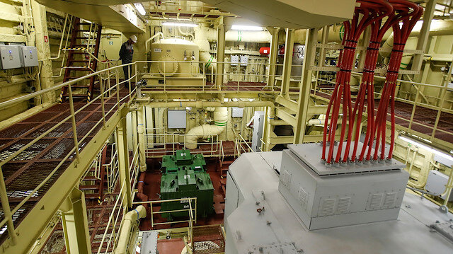 An employee looks on inside machinery compartment at floating nuclear power plant