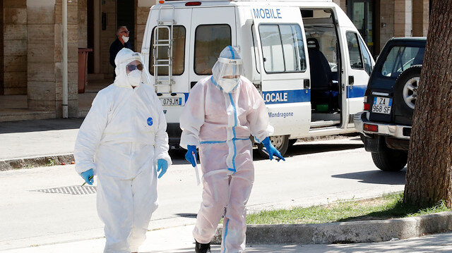 Healthcare workers in protective suits are seen near a residential complex, where 49 people tested positive for the coronavirus disease (COVID-19) and that was cordoned off after it was placed under quarantine, in the village of Mondragone, northwest of Naples, Italy, June 26, 2020.