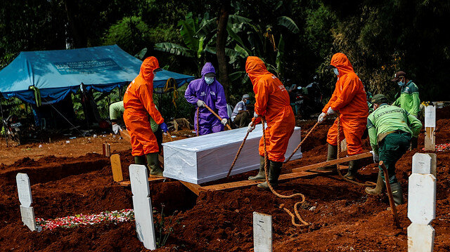 Workers wearing protective suits bury a coffin at the Muslim burial area provided by the government for victims of the coronavirus disease (COVID-19) at Pondok Ranggon cemetery complex in Jakarta, Indonesia, June 27, 2020