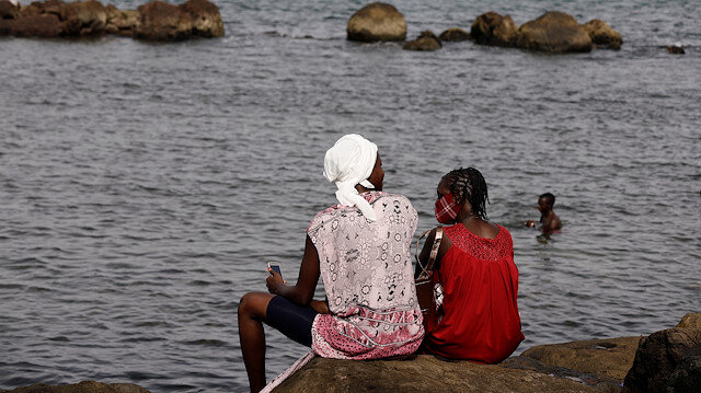 "Women sit on a rock at a beach called ""Plongeoir"", amid the outbreak of the coronavirus disease (COVID-19) in Dakar, Senegal June 28, 2020. REUTERS/Zohra Bensemra"
