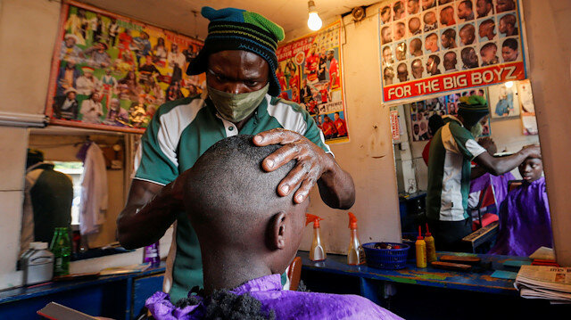 A barber wears a mask while shaving his client inside a barbershop named Old Trafford