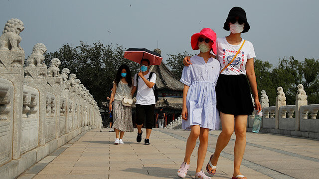 People wearing protective masks walk in the park at Summer Palace on a public holiday, after a new outbreak of the coronavirus disease (COVID-19), in Beijing, China, June 26, 2020. REUTERS/Thomas Peter