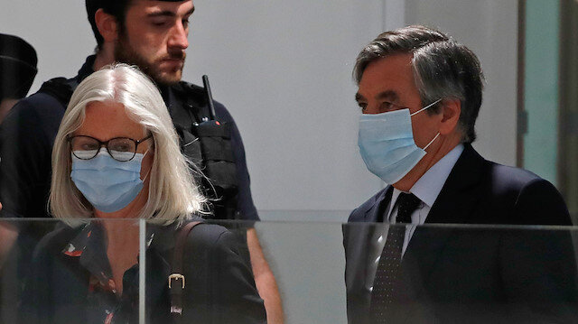 Former French prime minister Francois Fillon and his wife Penelope, wearing protective face masks, arrive for the verdict in their trial over a fake jobs scandal at the courthouse in Paris, France, June 29, 2020.