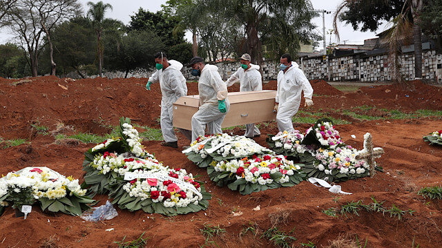 Gravediggers wearing protective suits carry the casket of a 63-year-old woman who died from the coronavirus disease (COVID-19), at Vila Formosa cemetery, in Sao Paulo, Brazil, June 26, 2020.