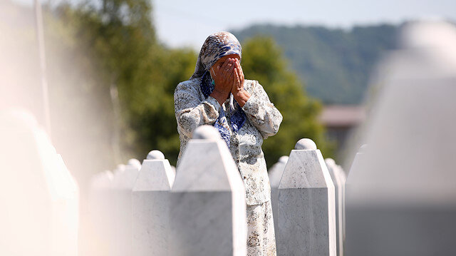 A woman prays at a graveyard, ahead of a mass funeral in Potocari near Srebrenica, Bosnia and Herzegovina July 11, 2020. Bosnia marks the 25th anniversary of the massacre of more than 8,000 Bosnian Muslim men and boys, with many relatives unable to attend due to the coronavirus disease (COVID-19) outbreak.