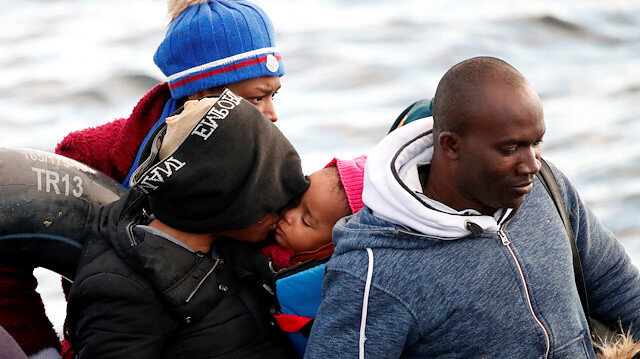 A migrant mother kisses her baby on board of a dinghy, following a failed attempt to cross to the Greek island of Lesbos, as a Turkish Coast Guard boat aproaches them on the waters of the North Aegean Sea, off the shores of Canakkale, Turkey, March 6, 2020. REUTERS/Umit Bektas