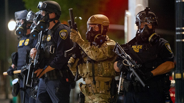 Federal law enforcement officers, deployed under the Trump administration's new executive order to protect federal monuments and buildings, face off with protesters against racial inequality in Portland, Oregon, U.S. July 18, 2020