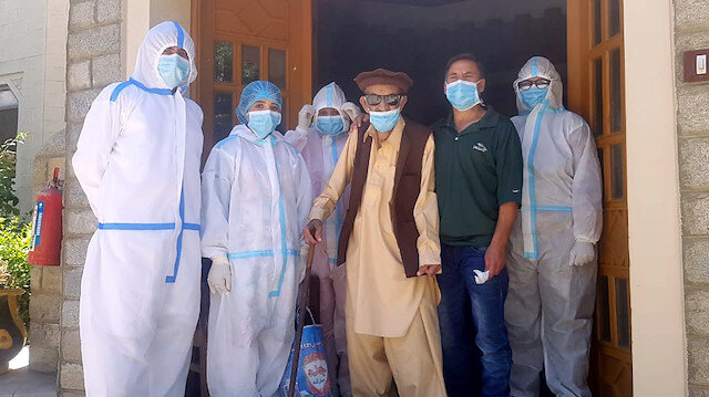 Abdul Alim, 103, stands with his son Suhail Aziz and staff members wearing personal protective equipment (PPE) in this group photograph taken after he recovered from coronavirus disease (COVID-19) and was discharged from the Aga Khan Health Services Emergency Response Centre in Booni, Chitral, Pakistan in this undated photograph provided to Reuters