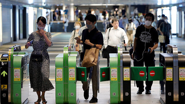 FILE PHOTO: Passengers wearing protective face masks pass through the automated entranceway at a station amid the coronavirus disease (COVID-19) outbreak in Tokyo, Japan July 23, 2020