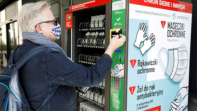 A man uses a vending machine for face masks