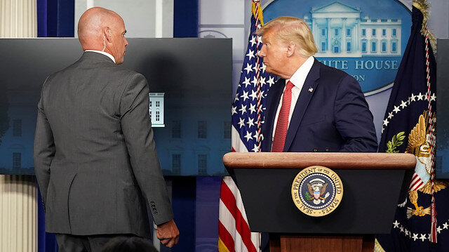 A Secret Service agent escorts U.S. President Donald Trump from a coronavirus disease (COVID-19) pandemic briefing after a shooting outside the White House in Washington, U.S., August 10, 2020.