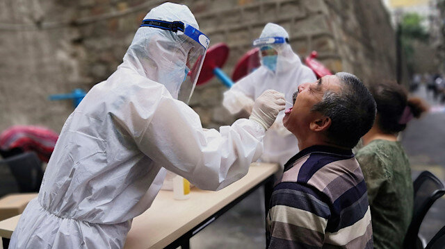 A medical worker in protective suit collects a swab from a man to conduct free nucleic acid tests for residents in the residential compound, after new cases of coronavirus disease (COVID-19) were found in Urumqi, Xinjiang province, China July 19, 2020