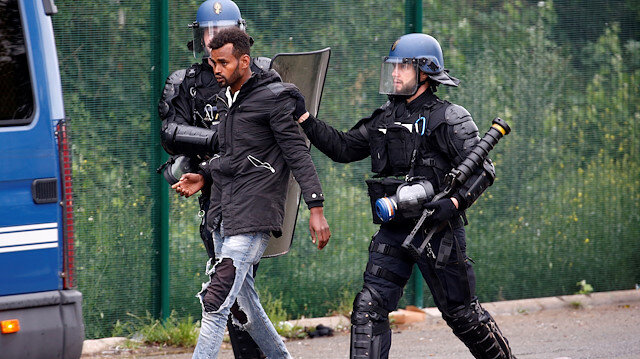 French police officers detain a migrant during the dismantling of a makeshift shelter camp