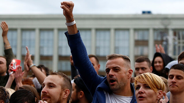 A man raises his fist as he attends an opposition demonstration to protest against presidential election results at the Independence Square in Minsk, Belarus, August 25, 2020.