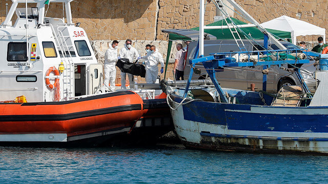 Emergency services carry a body at the dock of Le Castella after a migrant boat caught fire during rescue operations off the coast of Crotone, with some people still missing according to Italian media, Italy August 30, 2020.