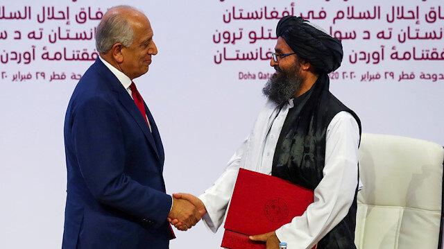 Mullah Abdul Ghani Baradar, the leader of the Taliban delegation, and Zalmay Khalilzad