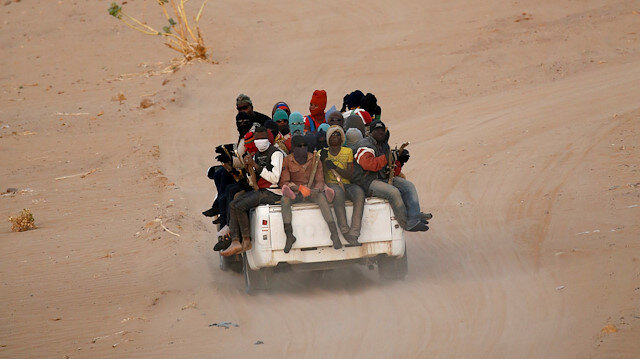 FILE PHOTO: Migrants crossing the Sahara desert into Libya ride on the back of a pickup truck outside Agadez, Niger, May 9, 2016.