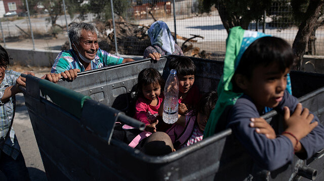Two men push a garbage bin with their belongings as children sit inside the bin, following a fire at the Moria camp for refugees and migrants on the island of Lesbos, Greece, September 11, 2020