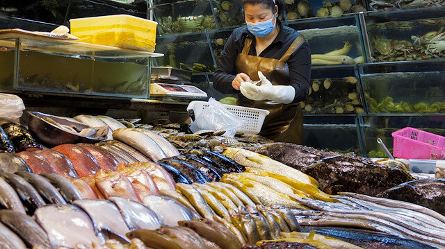 A woman works at a fish and seafood stall at a wet market following an outbreak of the coronavirus disease (COVID-19) in Beijing, China, August 14, 2020. REUTERS/Thomas Peter