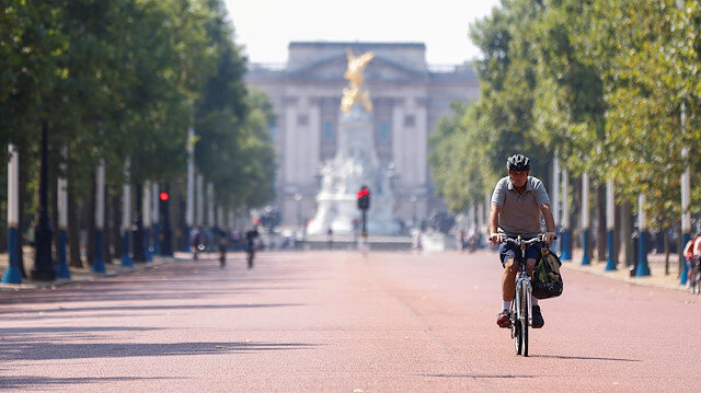 FILE PHOTO: A man cycles down The Mall, with Buckingham Palace in the background, in London, Britain, August 9, 2020.