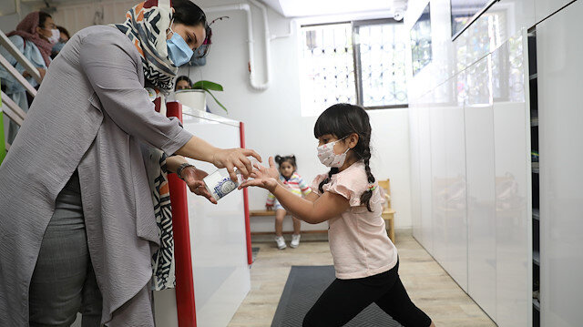 A girl wears a protective face mask gets her hands sanitized by her caretaker at Ghesseye Man (My Story) kindergarten, amid the outbreak of the coronavirus disease (COVID-19), in Tehran, Iran September 27, 2020. Picture taken September 27, 2020. Majid Asgaripour/WANA (West Asia News Agency) via REUTERS