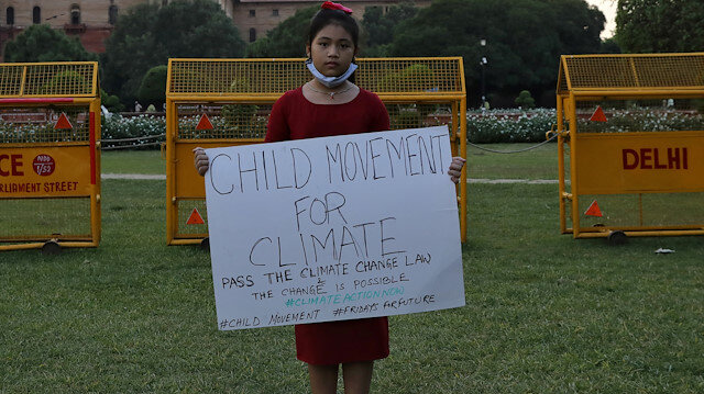 Licypriya Kangujam, 8, India's young climate activist, holds a poster during a protest demanding to pass a climate change law outside the parliament in New Delhi, India, September 23, 2020. Picture taken September 23, 2020. REUTERS/Anushree Fadnavis