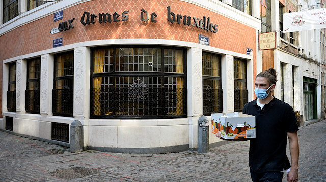 A man wearing a protective face mask walks past a restaurant, forced to close for four weeks, after a Belgian federal government decision in order to tackle a surging second wave of the coronavirus disease (COVID-19) in the country, in Brussels, Belgium October 19, 2020.