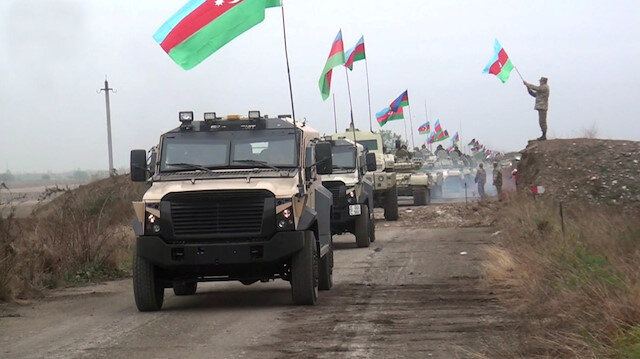 A still image from a video released by Azerbaijan's Defence Ministry shows military vehicles driving along a road as Azerbaijan army units enter the Aghdam region of Nagorno-Karabakh