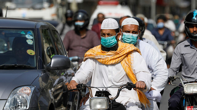 Men wear protective masks as they ride a motorcycle