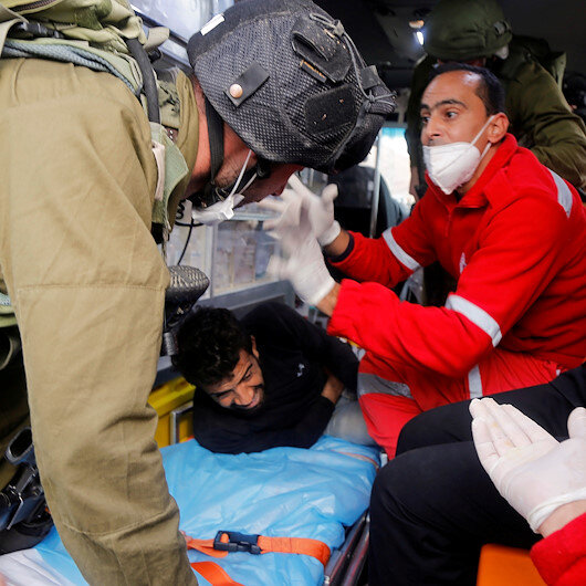 Israeli soldiers attempt to detain injured Palestinian