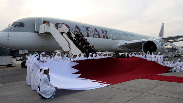 Qatar Airways staff hold a Qatari flag in front of an Airbus A350-1000