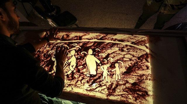 إدلب السورية.. فنان يرسم معاناة النازحين بالرمال