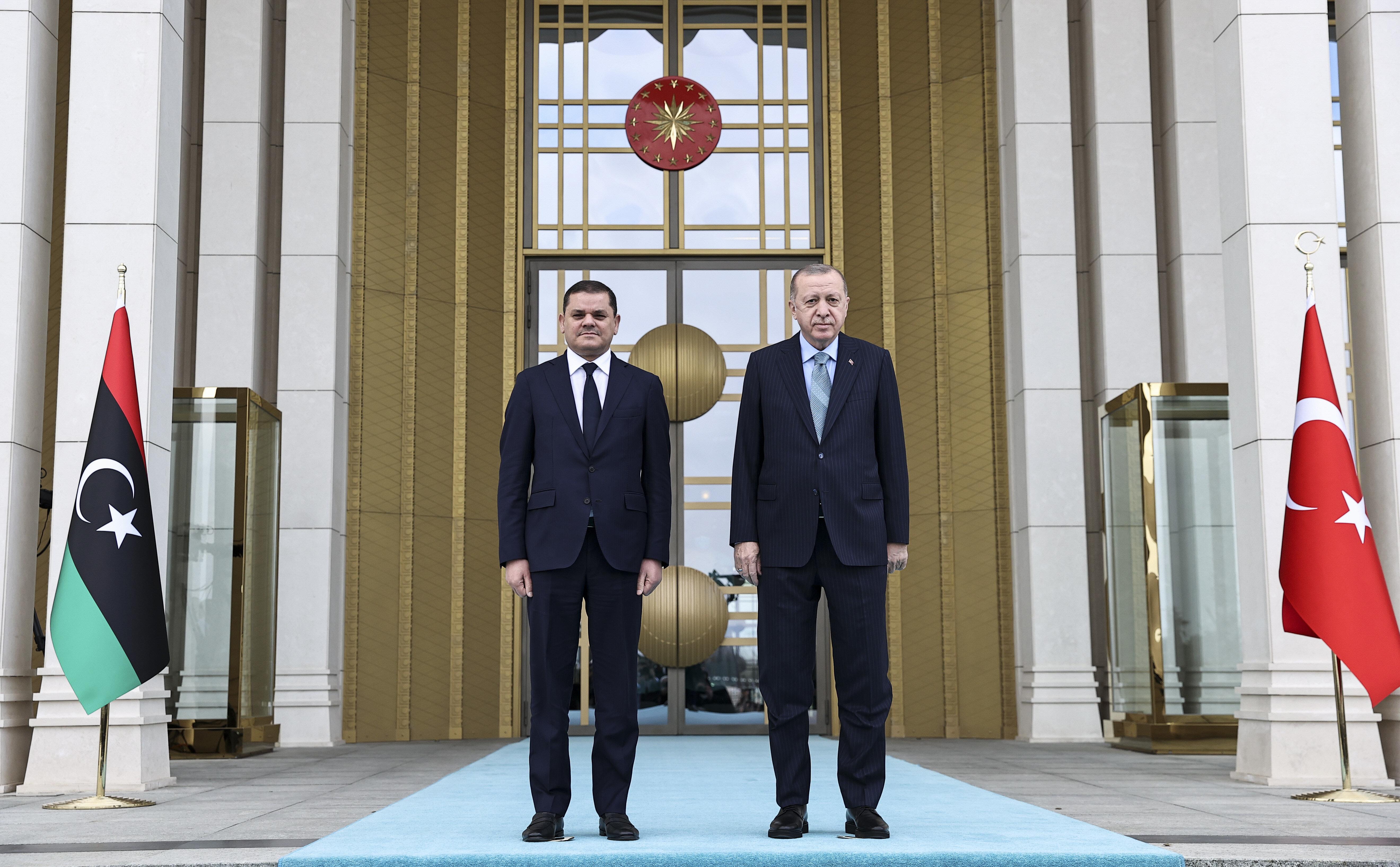 Erdoğan ve Dibeybe, merdivenlerde Türkiye ve Libya bayrakları önünde gazetecilere poz verdi.