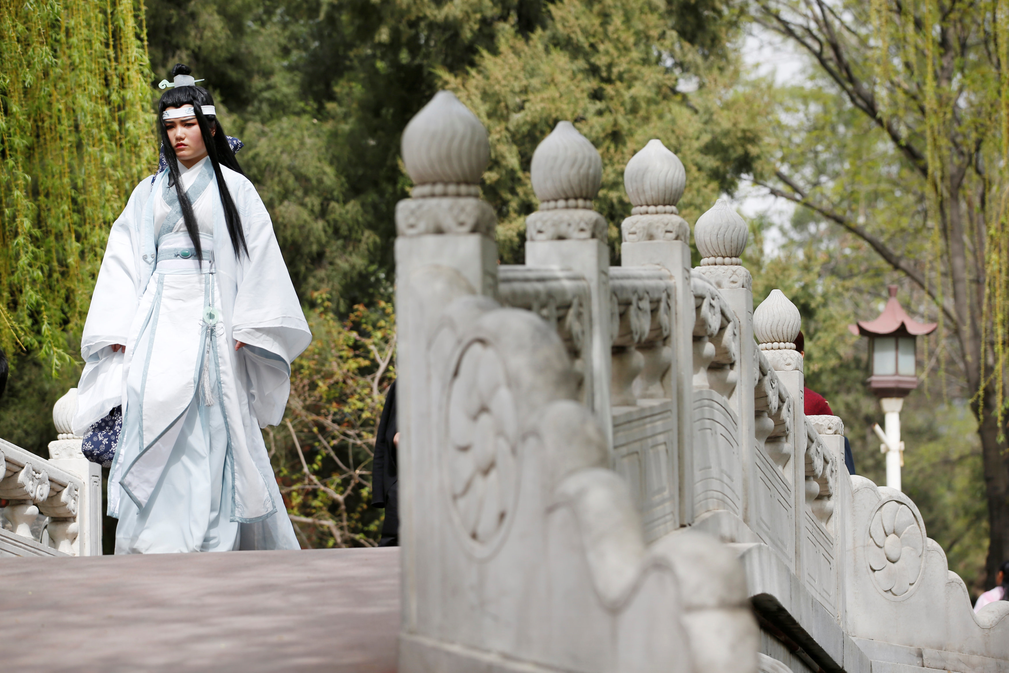 Women dressed in traditional costumes are seen during the Qingming tomb-sweeping festival in Beijing